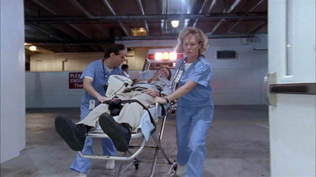 vídeos de stock, filmes e b-roll de low angle medium shot emts removing patient from ambulance on gurney / doctors wheeling him to emergency room - pronto socorro