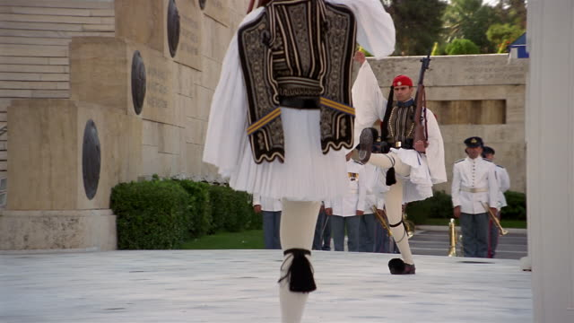 low angle medium shot evzones (greek guards) participating in the changing of the guard ceremony / athens, greece - bajonett stock-videos und b-roll-filmmaterial