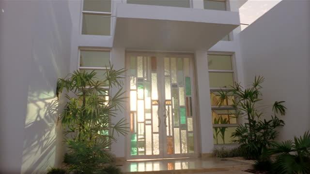 vídeos y material grabado en eventos de stock de low angle medium shot exterior of modern style house with stained glass windows - vidriera de colores