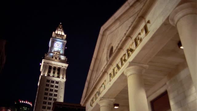 vídeos y material grabado en eventos de stock de low angle medium shot facade of quincy market building with u.s. customs house tower in background at night / boston, massachusetts - entabladura