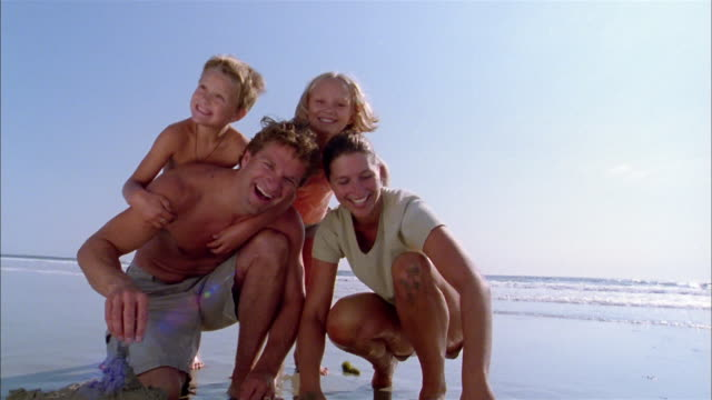 vídeos y material grabado en eventos de stock de low angle medium shot family posing together on beach and smiling at cam - vello pectoral