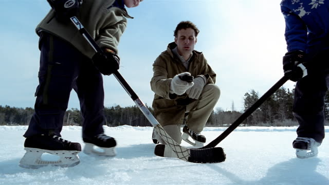 low angle medium shot father dropping hockey puck on ice / boys facing off with hockey sticks - hockey glove stock videos & royalty-free footage