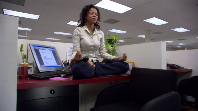 Low angle medium shot female office worker meditating in lotus position on desk in cubicle / answering phone / low angle