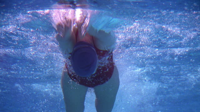 low angle medium shot female swimmer doing butterfly stroke towards camera / california - butterfly stroke stock videos and b-roll footage