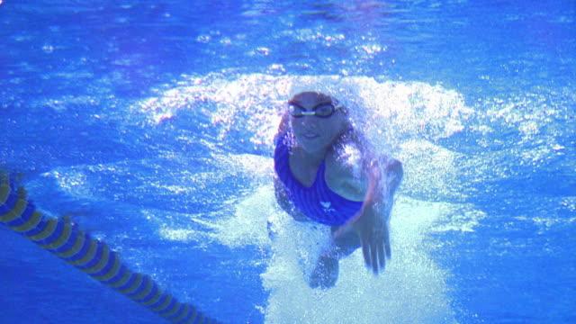 vidéos et rushes de low angle medium shot female swimmer doing freestyle stroke towards camera / california - natation
