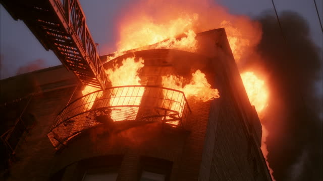 low angle medium shot fire burning on top floor of building with ladder extended up to fire escape - fire escape stock videos & royalty-free footage