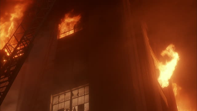 vidéos et rushes de low angle medium shot firefighter climbing ladder to fire on upper floor of warehouse - échelle