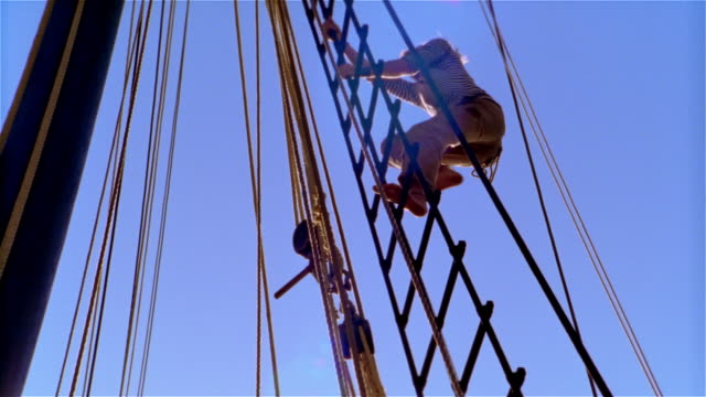 Low angle medium shot first mate climbing mast of ship