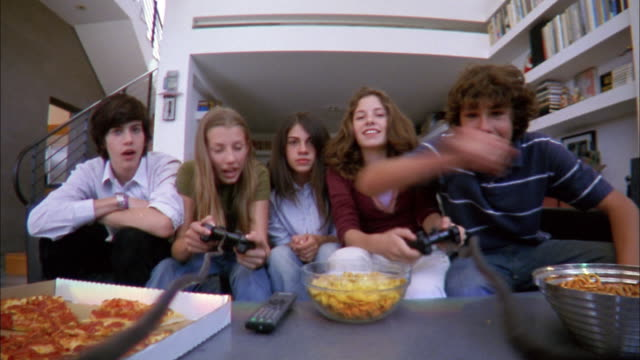 Low angle medium shot five teenagers facing CAM and playing home video games