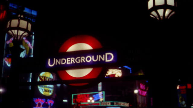 low angle medium shot focus underground subway sign and neon billboards at night / london - neon stock videos & royalty-free footage