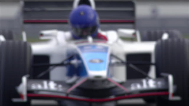 stockvideo's en b-roll-footage met low angle medium shot formula one race car hugging an s curve - racewagen