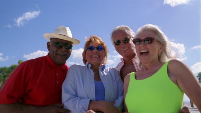 vídeos y material grabado en eventos de stock de low angle medium shot four seniors laughing and smiling at cam with blue sky in background - camisa de polo