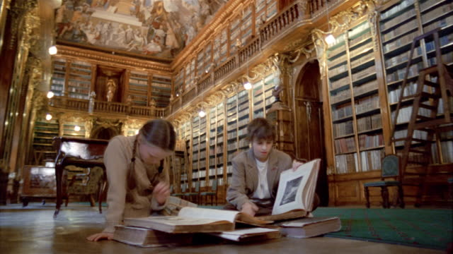 Low angle medium shot girl and boy reading books in Philosophical Hall library at Strahov Monastery / Prague