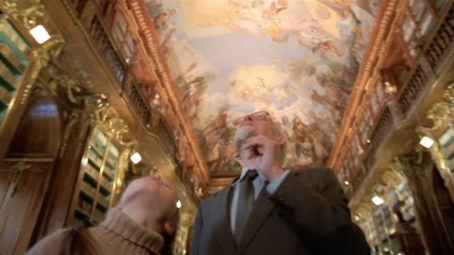 Low angle medium shot girl and old man looking at ceiling in Philosophical Hall library at Strahov Monastery / Prague