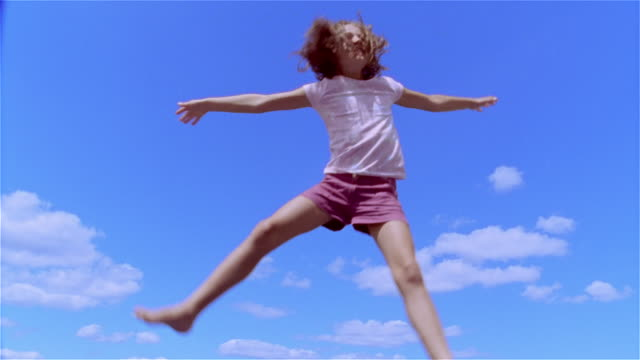 Low angle medium shot girl jumping on trampoline and smiling/ Saint-Ferme, France