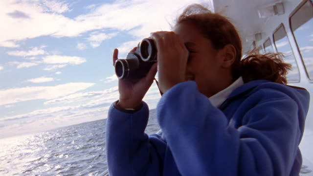 low angle medium shot girl on boat looking out over water with binoculars / blocking camera with her hand and walking away - whale watching stock videos & royalty-free footage