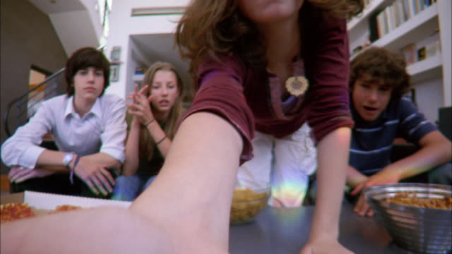 stockvideo's en b-roll-footage met low angle medium shot girl putting dvd into player / five teenagers leaning back and watching video in living room - dvd