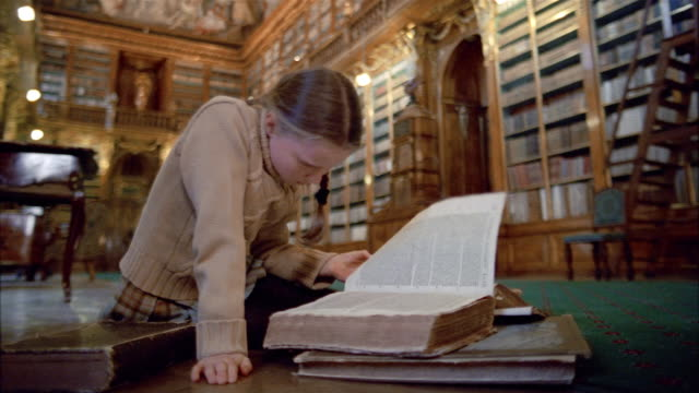 Low angle medium shot girl reading book on floor in Philosophical Hall library at Strahov Monastery / Prague