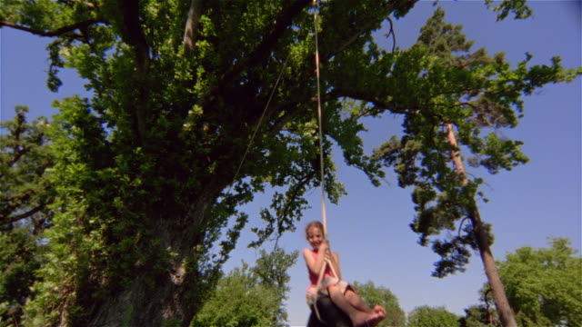low angle medium shot girl swinging on tire swing/ saint-ferme, france - tire swing stock videos & royalty-free footage