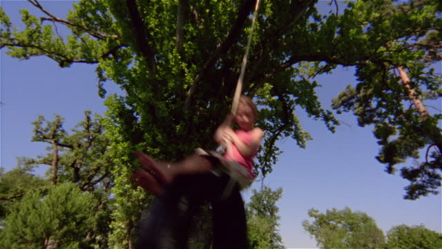 low angle medium shot girl swinging on tire swing/ saint-ferme, france - tyre swing stock videos & royalty-free footage