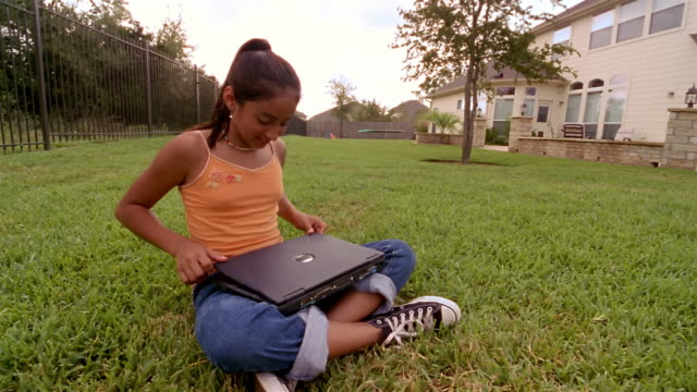 Low angle medium shot girl typing on laptop computer in backyard / smiling at CAM and walking toward house