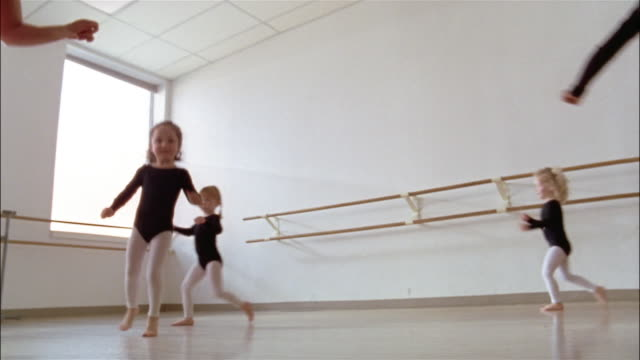 low angle medium shot girls wearing leotards and their teacher skipping around dance studio during ballet class - leggings stock videos & royalty-free footage