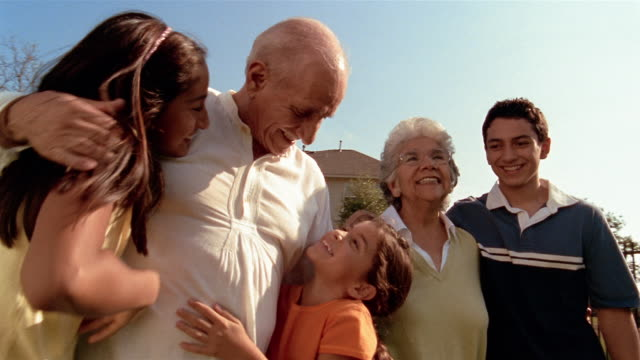 Low angle medium shot grandchildren running to hug grandparents in yard