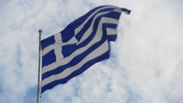 low angle medium shot greek flag waving in the breeze with cloudy sky in background - athens greece stock videos & royalty-free footage