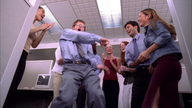 Low angle medium shot group of workers jumping and cheering / man dances in office