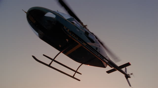 low angle medium shot helicopter taking off and flying away / mexico city - hubschrauber stock-videos und b-roll-filmmaterial