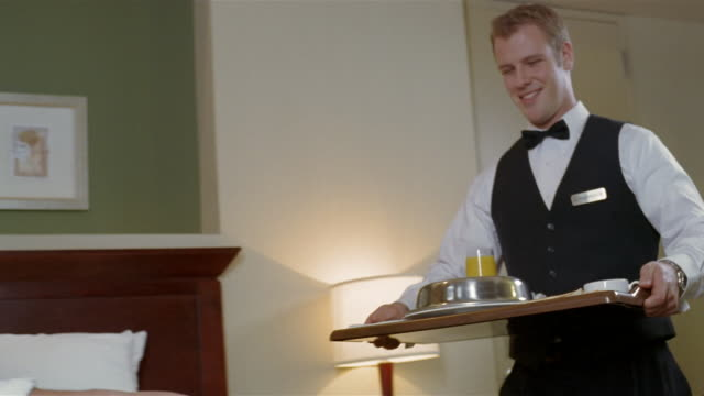 Low angle medium shot hotel employee delivering tray of room service breakfast to businessman talking on cell phone in hotel room / placing tray on bed and removing lid