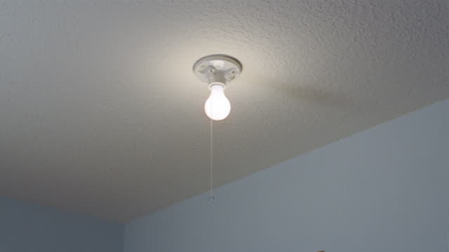 low angle medium shot illuminated light bulb / hand reaching up and pulling pull cord / turning off light - pulling stock videos & royalty-free footage