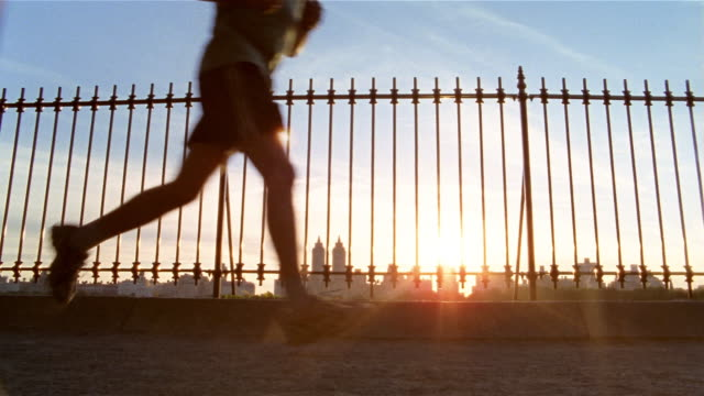 Low angle medium shot joggers running around Central Park Reservoir at sunset / sun shining through fence / New York