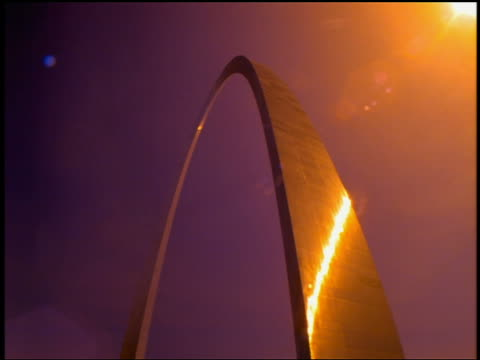 Low angle medium shot light from time lapse sunrise reflecting on side of Gateway Arch / St. Louis, Missouri