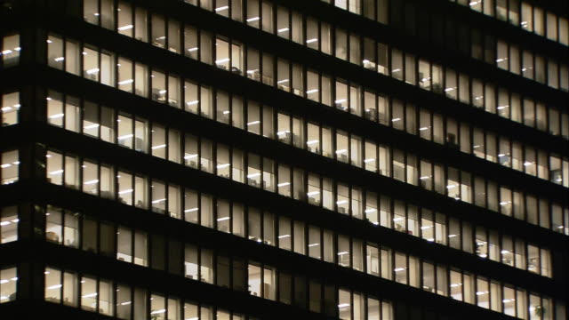 low angle medium shot lights on in windows of office building at night / west shinjuku, tokyo, japan - fluorescent light stock videos & royalty-free footage
