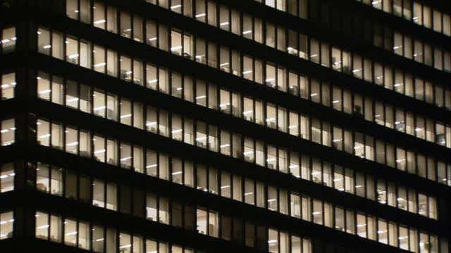 low angle medium shot lights on in windows of office building at night / west shinjuku, tokyo, japan - office block exterior点の映像素材/bロール