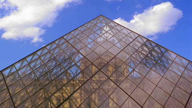 Low angle medium shot Louvre Pyramide / time lapse clouds moving in background
