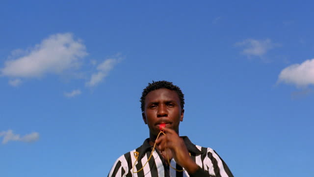 Low angle medium shot male Black referee blowing whistle and holding up red card during soccer game