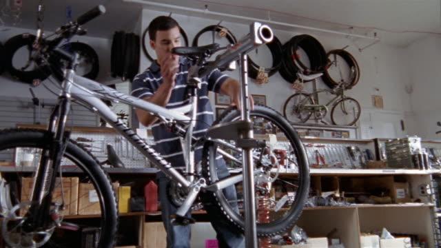 low angle medium shot man adjusting seat on bicycle in bike shop / spinning tires - bicycle seat stock videos & royalty-free footage