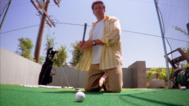 vídeos de stock, filmes e b-roll de low angle medium shot man aiming and hitting golf ball toward cam w/putter handle / cheering - bolsa de golfe
