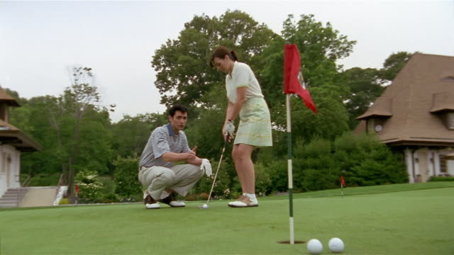 low angle medium shot man and woman on putting green / zoom out zoom in man instructing woman / woman making putt - golf shoe stock videos & royalty-free footage
