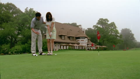 low angle medium shot man and woman putting on green / man instructing woman / woman making final putt - golf shoe stock videos & royalty-free footage