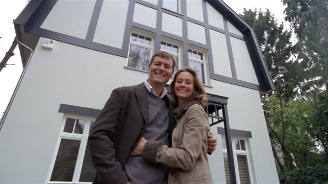 Low angle medium shot man and woman standing in front of house hugging / smiling at CAM