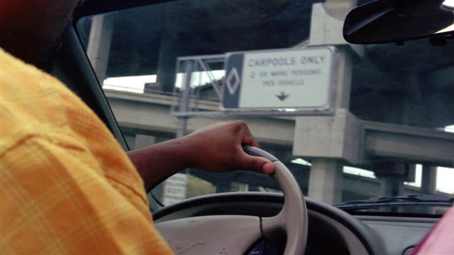 Low angle medium shot man driving convertible on I-10 freeway / east of Los Angeles, California