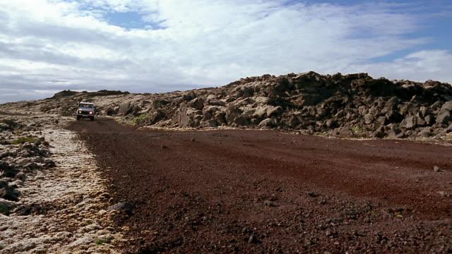 vídeos y material grabado en eventos de stock de low angle medium shot man driving land rover through lava field near the blue lagoon (blaa loninu) / iceland - paisaje volcánico