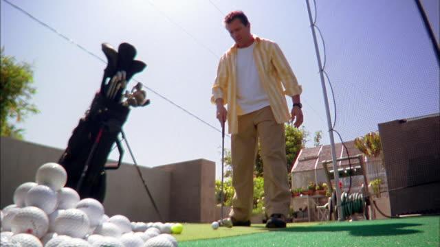 vídeos de stock, filmes e b-roll de low angle medium shot man hitting golf balls w/driver on rooftop practice green - bolsa de golfe