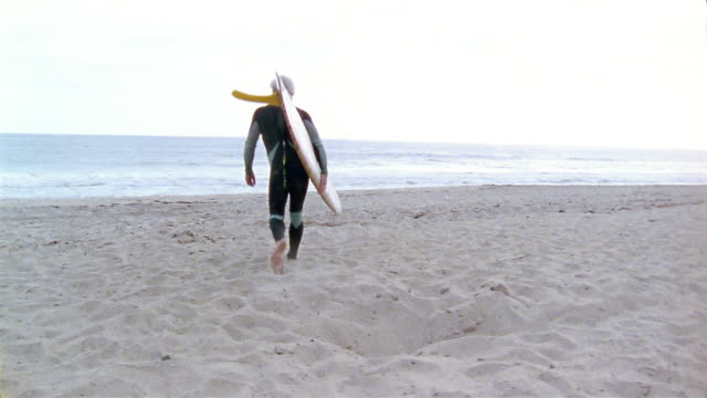 vídeos de stock, filmes e b-roll de low angle medium shot man holding surfboard walking on beach towards water - homens maduros