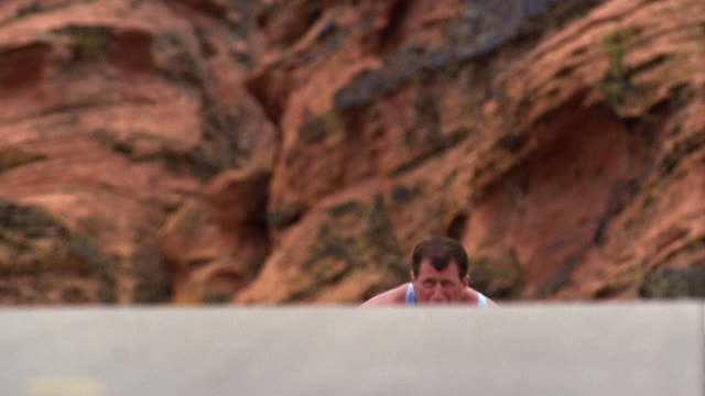 Low angle medium shot man in racing wheelchair climbing hill in Red Rock Canyon