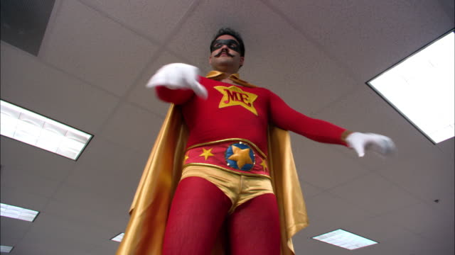 Low angle medium shot man in superhero costume saluting, leaping and running off in office / Los Angeles