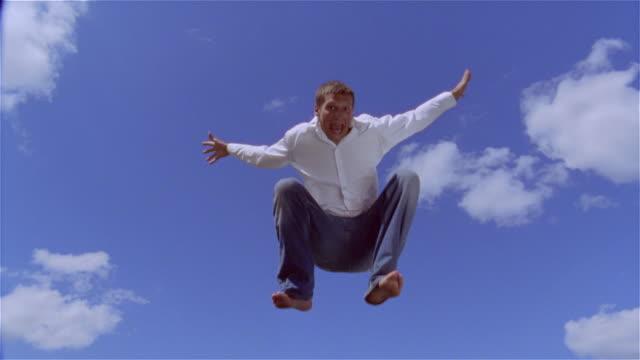 low angle medium shot man jumping on trampoline/ saint-ferme, france - トランポリン点の映像素材/bロール
